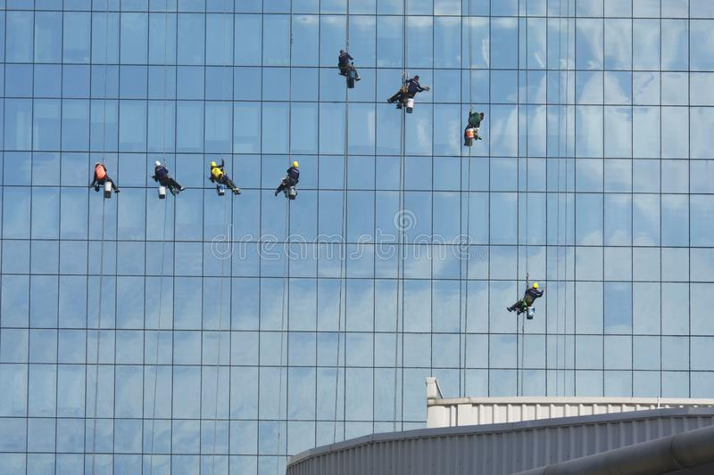 Hanging men cleaning a mirror wall of a high building. Yesterday I went to a big department store in town far away from home and take pictures stock images