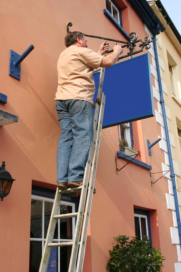 Hanging a New Sign stock image