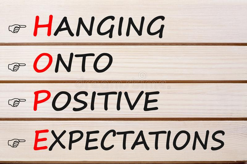 Hanging Onto Positive Expectations HOPE. Hanging Onto Positive Expectations words with HOPE written on wood wall decor. Business concept royalty free stock photography