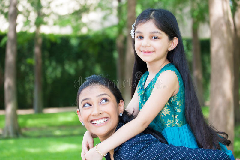 Hanging out with fam. Closeup portrait, family having fun hanging out, girl sitting on top women shoulders, green trees outdoors background stock photography