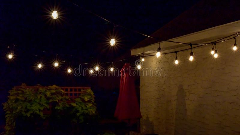 Hanging outdoor lights over patio in summer night stock photos