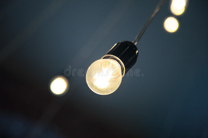 Hanging retro light bulb in the cafe or coffee shop interior design loft style modern vintage decoration.  royalty free stock photo