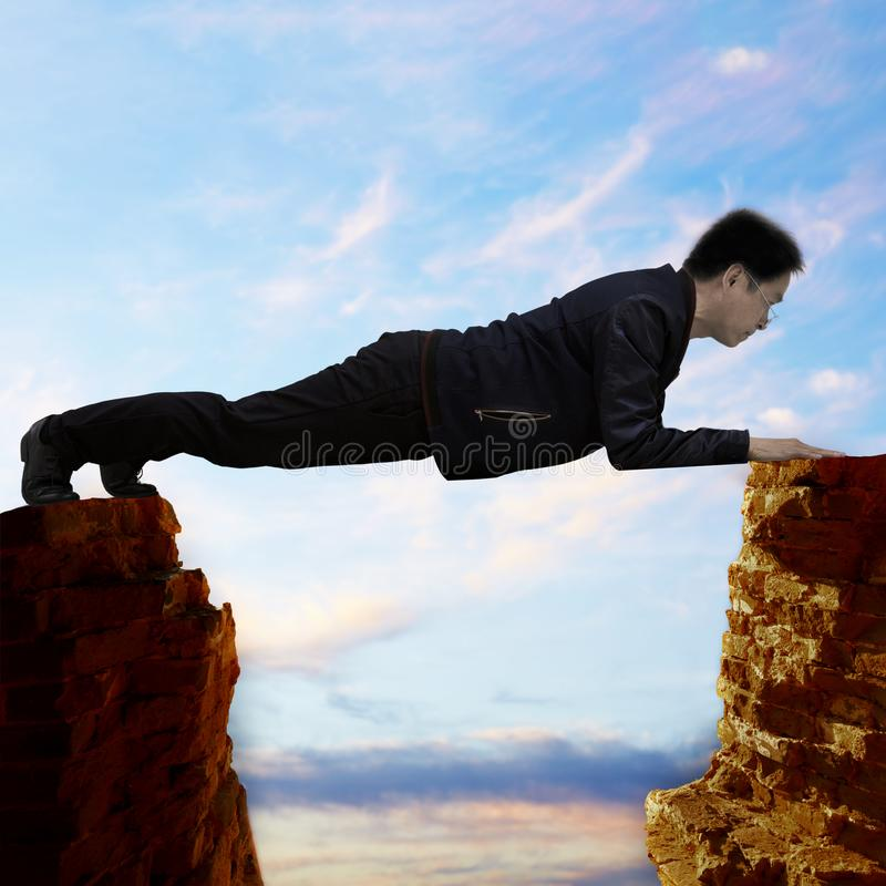 Middle-age man hanging between problem and trouble. A man hanging between a rock and a hard place. Concept picture, tough situation of stress, effort and royalty free stock photos