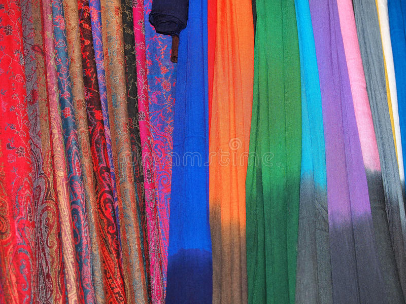 Hanging scarfs. Pile of gentle folded shawls (scarfs) hanging at the market stock photo