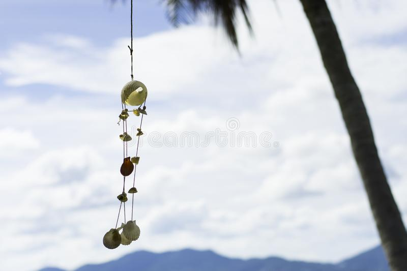 Hanging seashells chime together with every gentle breeze,summer season. Hanging seashells chime together with every gentle breeze, making a soft, soothing music royalty free stock photography