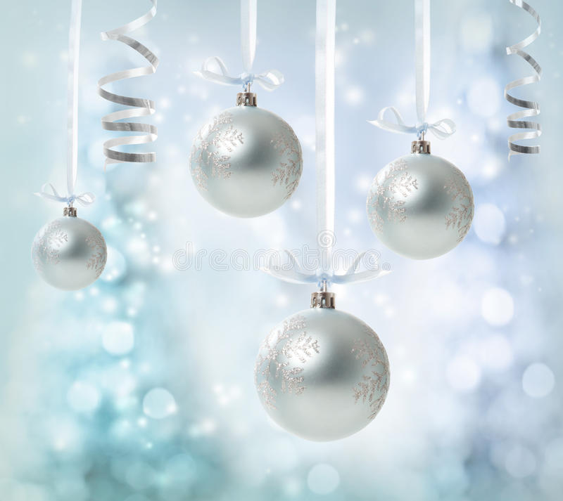 Hanging Silver Christmas Ornaments. Silver Christmas Ornaments over glowing tree background royalty free stock images