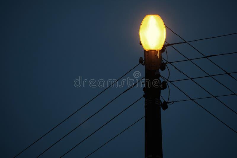 A hanging street lamp against a serene dark sky. Art stock photography