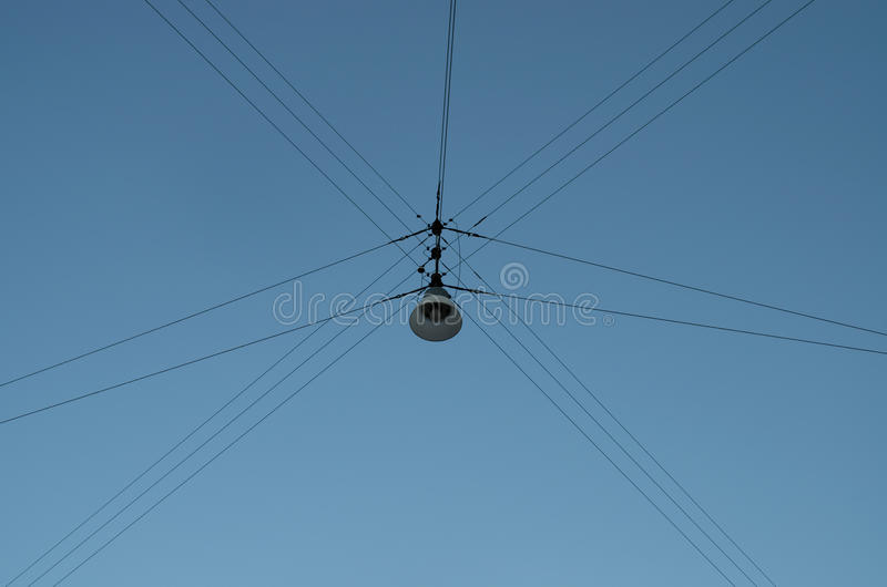 Hanging street lamp. A hanging street lamp with an interesting wire pattern stock photos