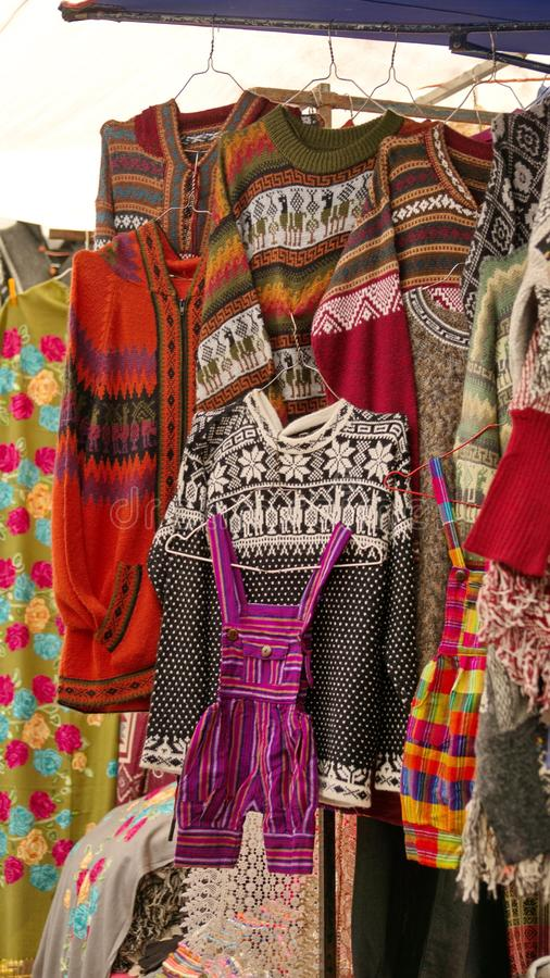 Hanging sweaters and coveralls. Colorful sweaters and children`s coveralls hanging in the Artisan`s Market in Otavalo, Ecuador royalty free stock photo