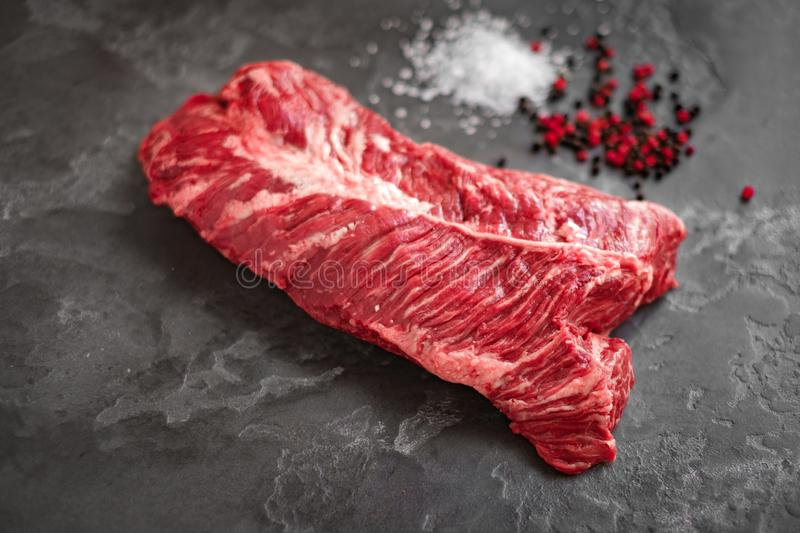 Hanging Tender steak on a stone background with salt and pepper - onglet steak. Raw Hanging Tender steak on a stone background with salt and pepper - onglet stock photography