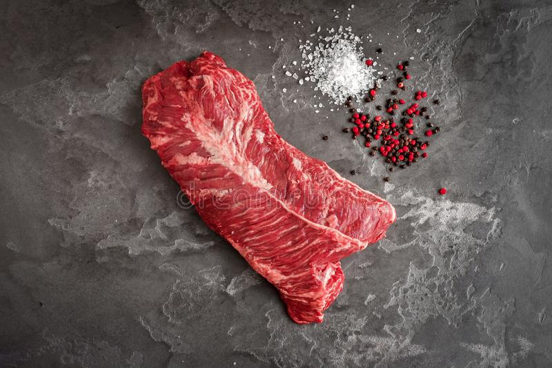 Hanging Tender steak on a stone background with salt and pepper - onglet steak. Top view stock image