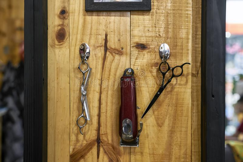 Hanging tools for haircut in barbershop with wooden walls royalty free stock photography