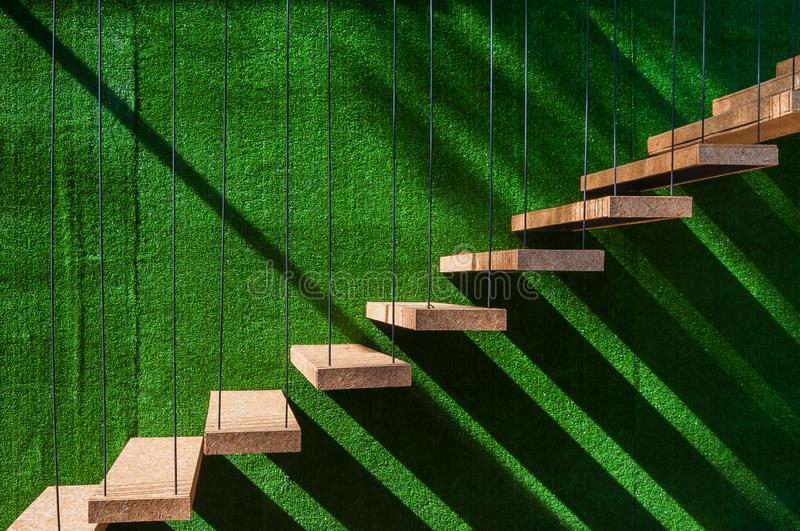 Hanging wooden stairs on artificial grass wall background Apartment staircase made of cables and wood apparently floating royalty free stock photography