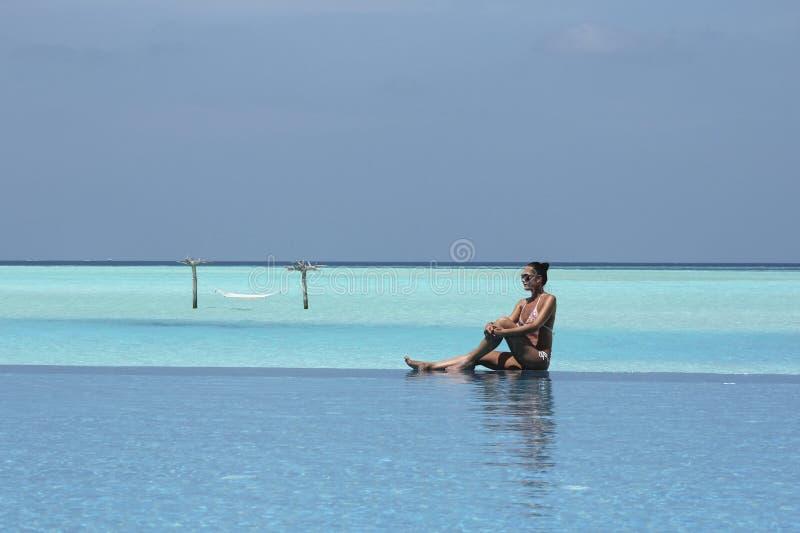 Hangmat in water en meisje in de Maldiven en oneindigheidspool stock afbeelding