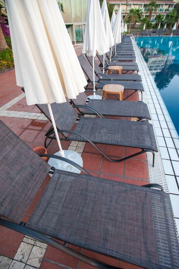 Hangmatten met paraplu's door de pool voor gasten royalty-vrije stock foto