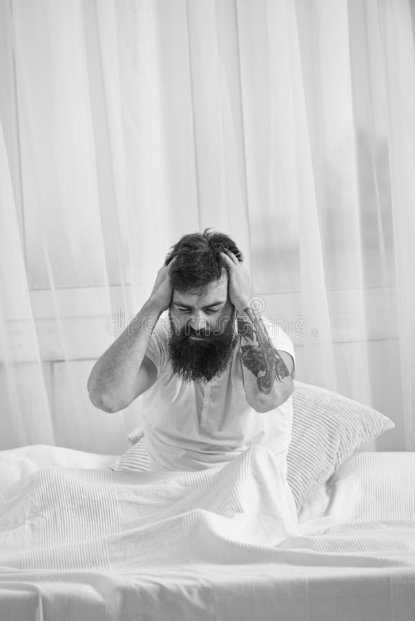 Hangover concept. Man in shirt sits on bed awake, white curtain on background. Guy on disappointed painful face waking. Up in morning. Macho with beard and stock images