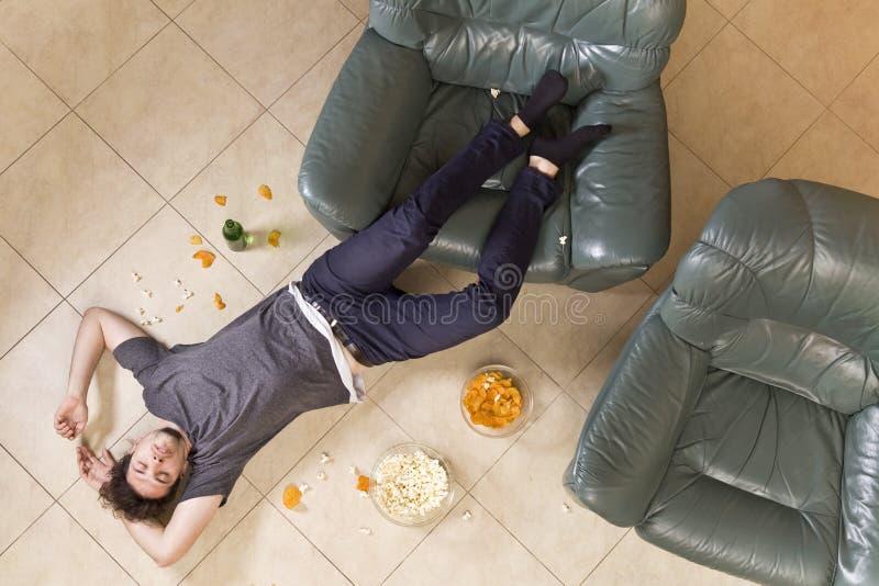 hangover Homem novo que encontra-se no assoalho após o partido home Vista superior fotos de stock royalty free