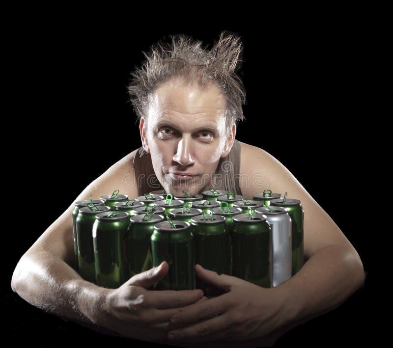 hangover O homem bêbedo e é muitas latas de cerveja vazias imagem de stock