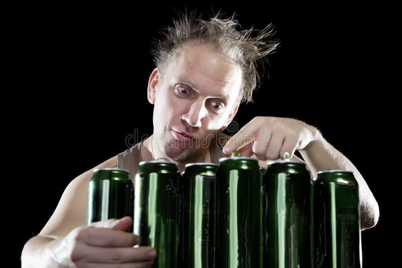 hangover O homem bêbedo e é muitas latas de cerveja vazias fotos de stock