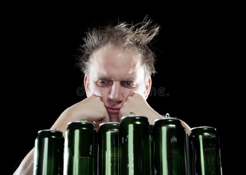 hangover O homem bêbedo e é muitas latas de cerveja vazias imagens de stock