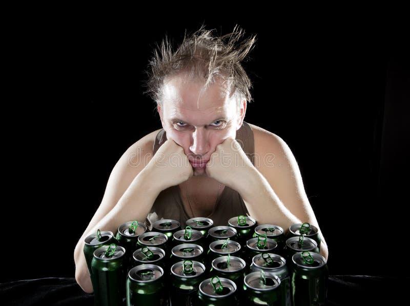 hangover O homem bêbedo e é muitas latas de cerveja vazias foto de stock