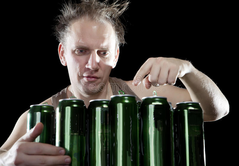 hangover O homem bêbedo e é muitas latas de cerveja vazias foto de stock royalty free