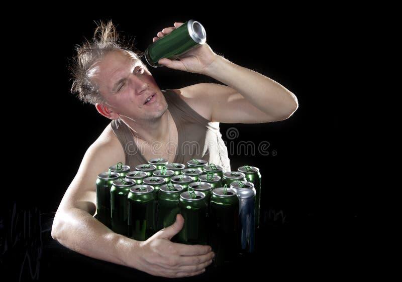 hangover O homem examina, se não há nenhuma gota da cerveja em uma lata foto de stock