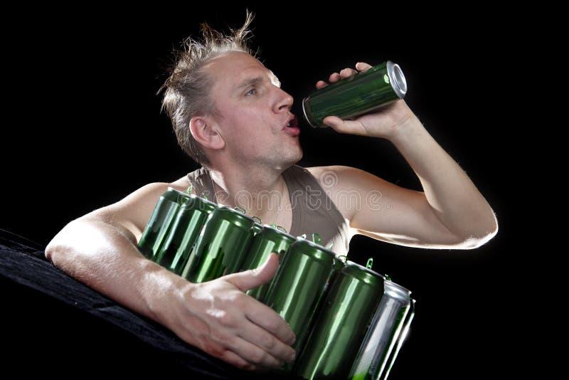 hangover O homem examina, se não há nenhuma gota da cerveja em uma lata fotos de stock