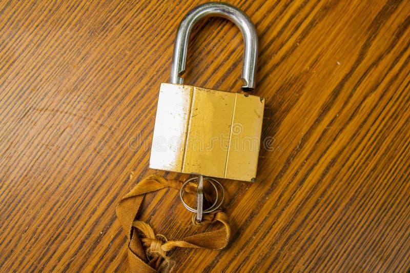 Hangslot met sleutel op de band op een houten achtergrond royalty-vrije stock foto