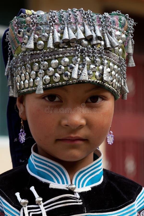 Hani people, China. YUANYANG, CHINA - MAY 05: Hani shoolgirl poses for a photo during Yuanyang festival on May 05, 2014 in Yuanyang, China stock photo