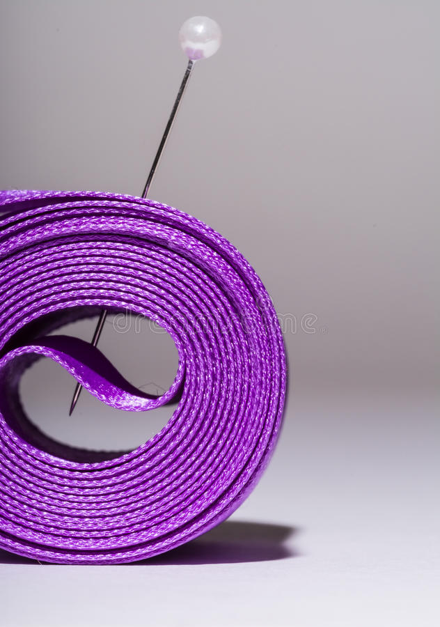 Hank silk purple ribbon with a pin, close-up, macro on a grey. Background royalty free stock photography
