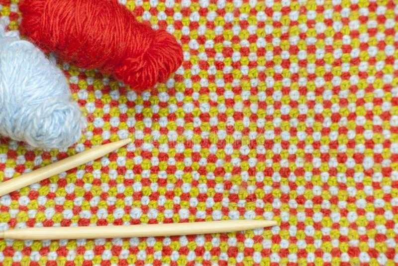 Hanks do fio e de agulhas de confecção de malhas vermelhos, azuis no fundo do pano feito malha, de lã fotografia de stock