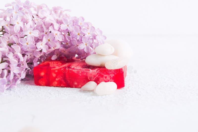 Hanmade tvål med vita stenar och lila blommor aromatherapy begreppsbrunnsort arkivfoto