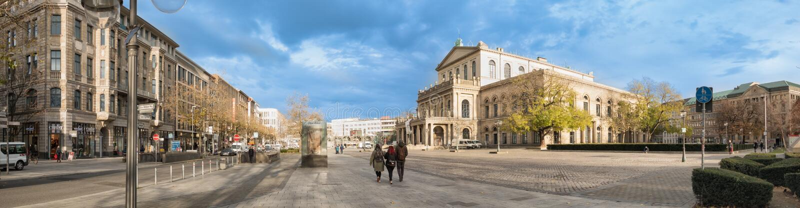 HANNOVER, ALEMANHA - 23 DE NOVEMBRO DE 2017: Os pedestrants não identificados cruzam o lugar do ganrd na frente do teatro da óper imagens de stock