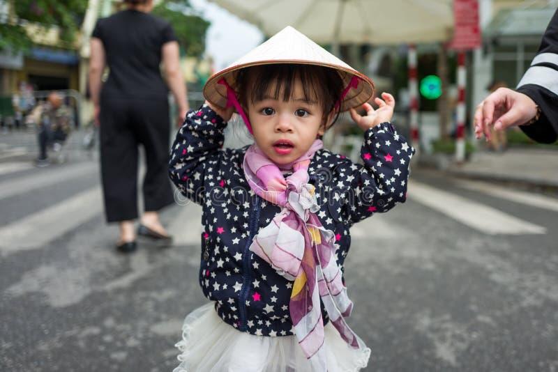 Hanoï, Vietnam - 15 avril 2018 : La jeune fille avec le chapeau traditionnel regarde l'appareil-photo à Hanoï photographie stock