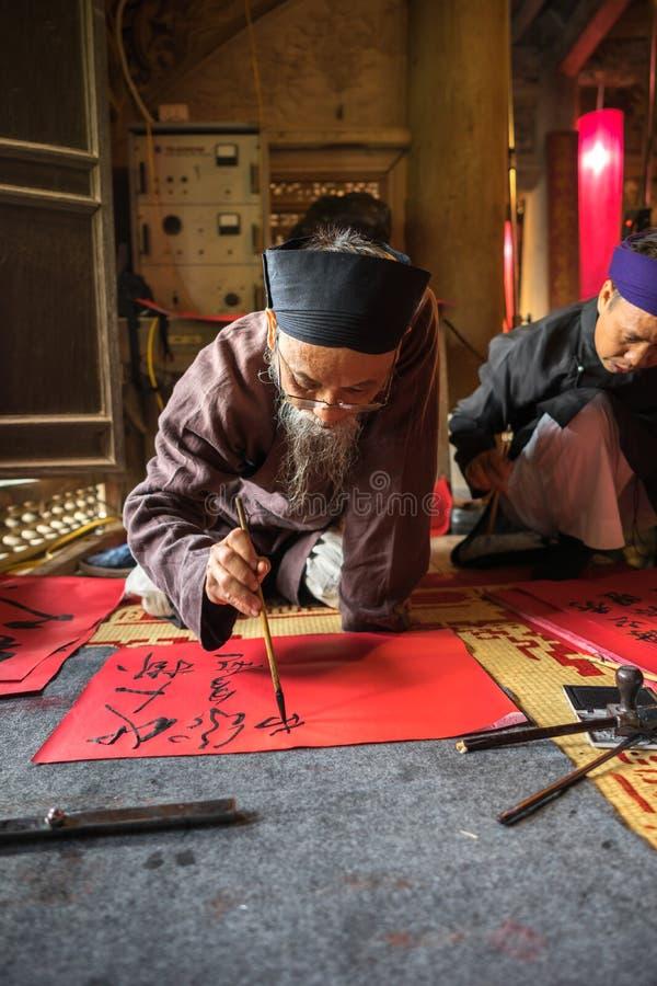 Hanoï, Vietnam - 22 juin 2017 : Le chercheur écrit les caractères chinois de calligraphie dans la maison communale ainsi au villa photo stock