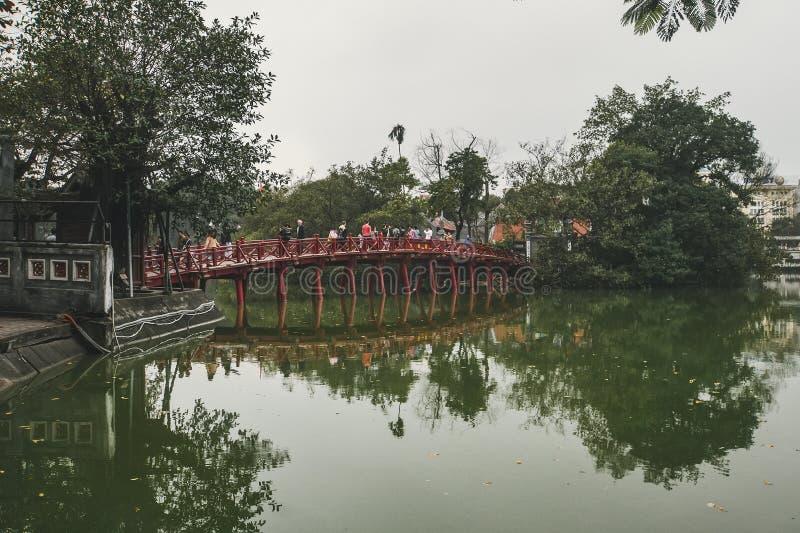 Hanoi r?d bro Den tr?r?d-m?lade bron ?ver Hoan Kiem sj?n f?rbinder kusten och Jade Island p? som den Ngoc sonen arkivbilder