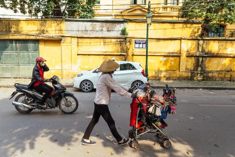 Hanoi ulica z mężczyzna napędową kobietą z i motocyklem wisząca ozdoba handlu detalicznego furą i poruszającym samochodem w Wietn obraz royalty free