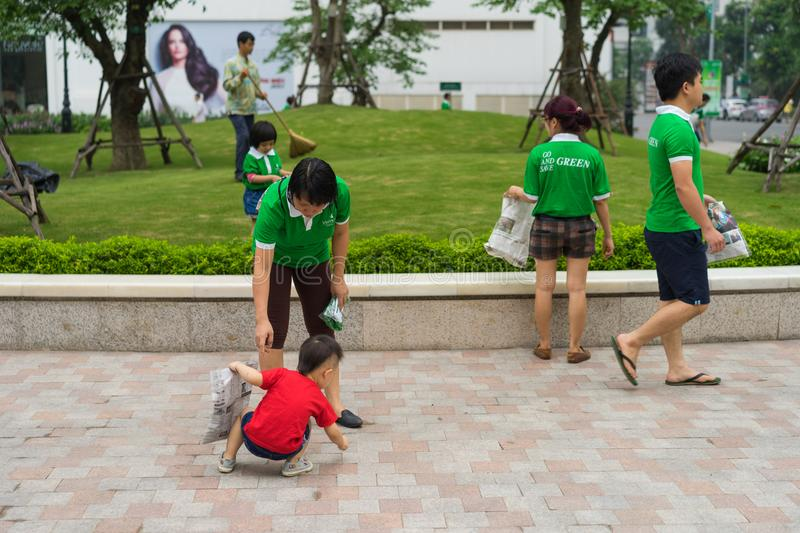 Hanoi, Vietnam - Apr 19, 2015: Family volunteers picking up litter in the park at Times City, a luxury and high class combination royalty free stock photo