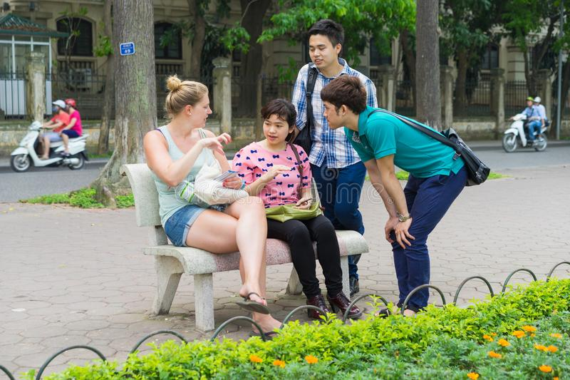 Hanoi, Vietnam - Apr 5, 2015: Group of students learn to speak English with English native foreigner people at Hoan Kiem lake. A l royalty free stock photos
