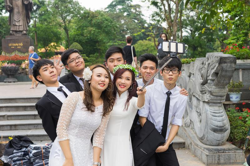 Hanoi, Vietnam - Apr 5, 2015: Group of students in Vietnamese traditional dress Ao Dai taking photo for memory at Ly Thai To park,. Dinh Tien Hoang street, by royalty free stock photo