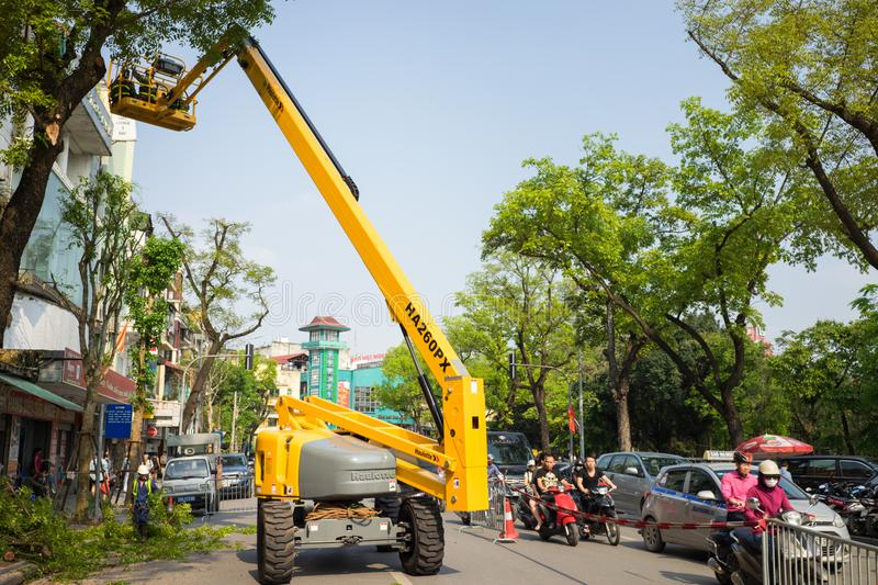Hanoi, Vietnam - Apr 24, 2016: Mechanical platform to make tree pruning on Dinh Tien Hoang street, center of Hanoi capital.  stock photos