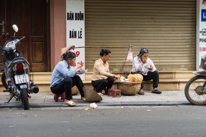 Hanoi, Vietnam - Apr 5, 2015: People have food on sidewalk in Luong Ngoc Quyen street.  royalty free stock photos