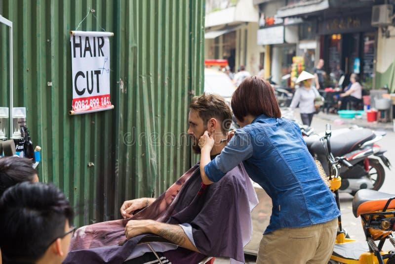 Hanoi, Vietnam - 5 April, 2015: De niet geïdentificeerde vrouwelijke kapper sneed haar op straat in Hanoi, Vietnam Kapper die doe stock foto's
