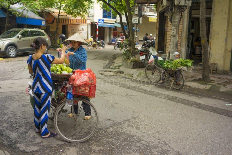 Hanoi Vietnam - April 13, 2014: Den oidentifierade matförsäljaren säljer frukter som bärs av cykeln till en kvinna på den Hanoi g royaltyfria foton