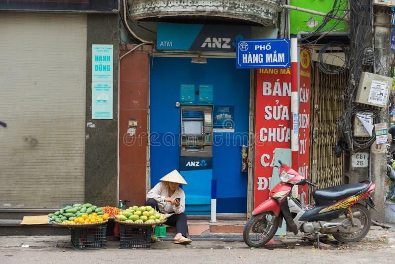 Hanoi Vietnam - April 5, 2015: Försäljareförsäljningsfrukt framme av ANZ ATM i den Hang Mam gatan, Hanoi arkivfoton