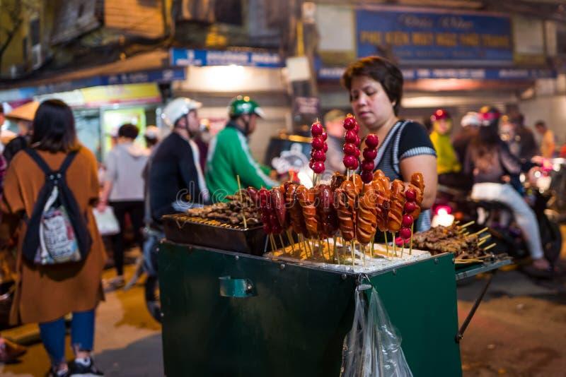 Hanoi Vietnam - April 15, 2018: Försäljaren säljer gatamat i Bia Hoi Corner i Hanoi royaltyfri fotografi