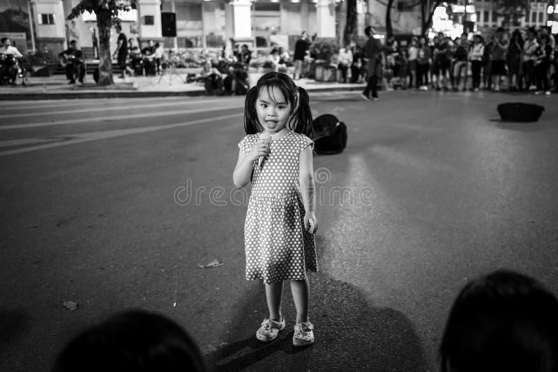 Hanoi, Vietnam - 13. April 2018: Junge Mädchen isst Eiscreme in Verkehr-beruhigtem Bereich von Hanoi stockfoto
