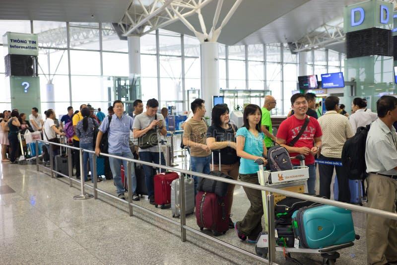 Hanoi, Vietnam - 29 April, 2016: Rij van Aziatische mensen in lijn die bij het inschepen van poort in Noi Bai-luchthaven wachten stock foto's