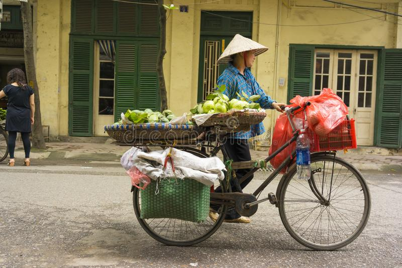 Hanoi, Vietnam - April 13, 2014: Unidentified food vendor sells fruits carried by bike on Hanoi street, Vietnam. The old looked ho. Use on background royalty free stock photography